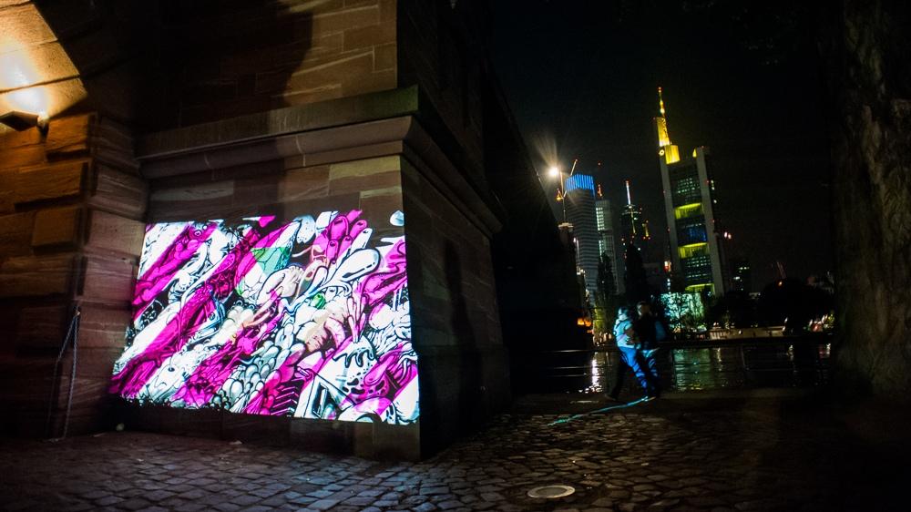 Mitten im Frankfurter Bankenviertel war der Digital Paintroller zu sehen. Die Skyline von Frankfurt erstreckt sich darüber.