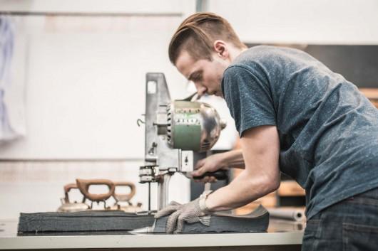 Johann Ruttloff schneidet Jeansstoff für CROMATICS. Die Taschen entstehen in reiner Handarbeit.