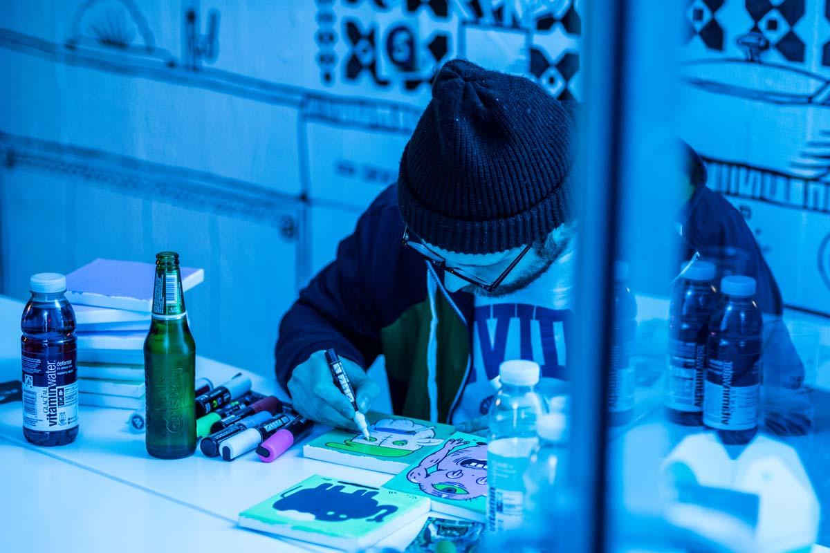 Einer der Künstler zeichnet auf ein Buch.