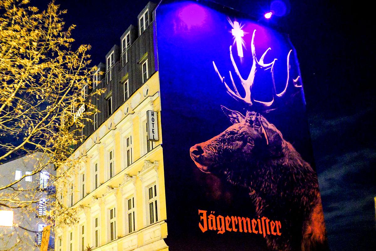 Nachts leuchtet der Hirsch von Jägermeister an der Berliner East Side Gallery. UV Farben bringen die Wand zum Leuchten.