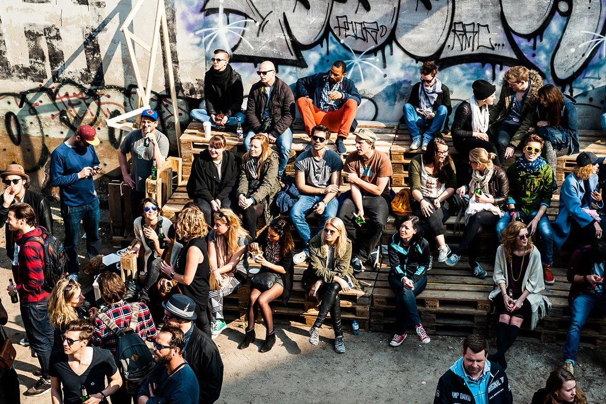 Das Wetter stimmt bei der Converse Clash Wall in Berlin. Das Publikum verfolgt die Arbeit der Künstler, die CROMATICS durch Künstlerakquise aus ihrem Künstlerportfolio gebucht hat. Es gibt kühles Bier und das Publikum geniesst die Sonne auf EURO-Paletten.