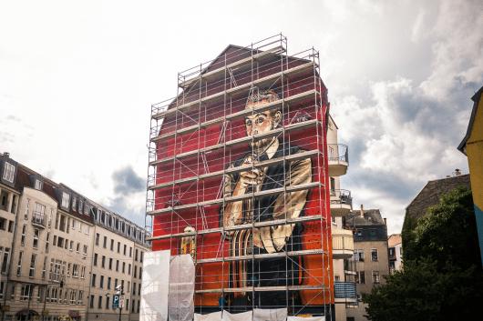 Die Wand steht noch eingerüstet. Das Graffitibild wird aber bald enthüllt.