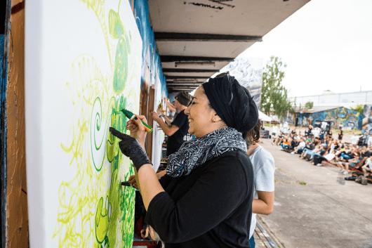 Die Künstler malen vor einem Publikum auf großen Leinwänden.