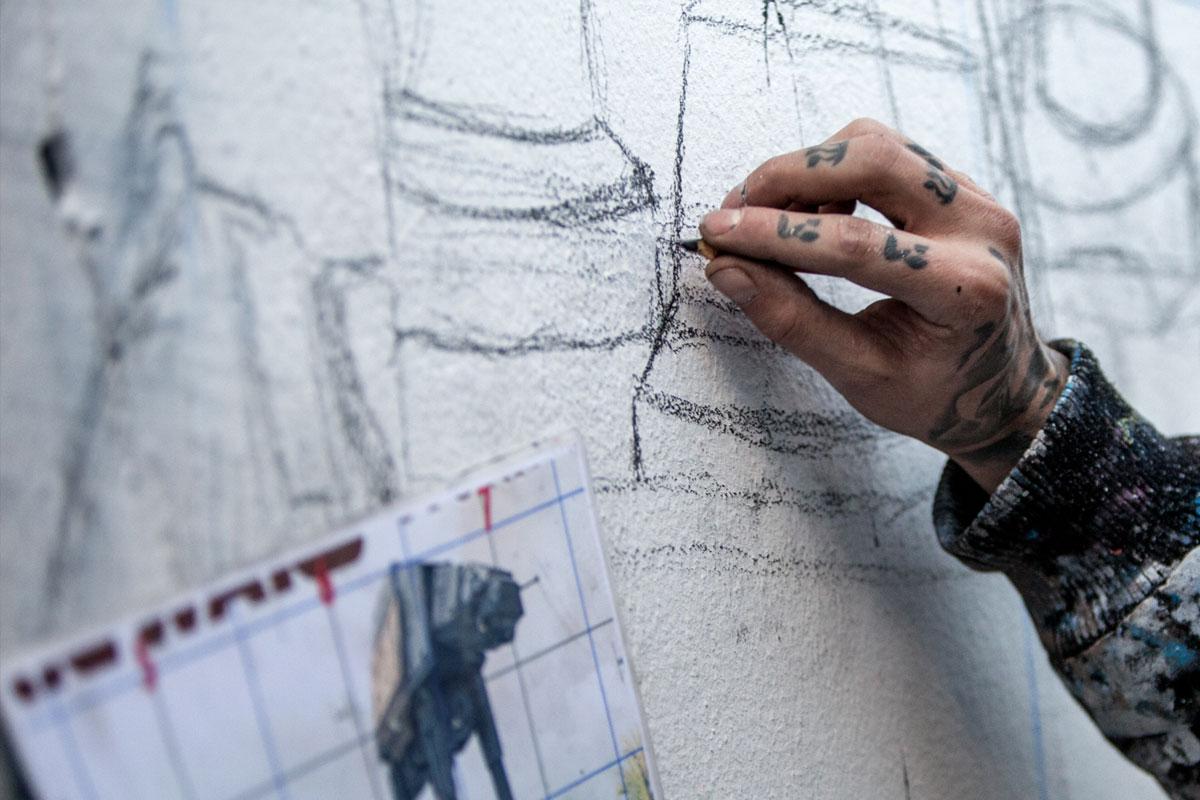 Die Graffitikünstler malen mit Bleistiften ihre Raster vor.