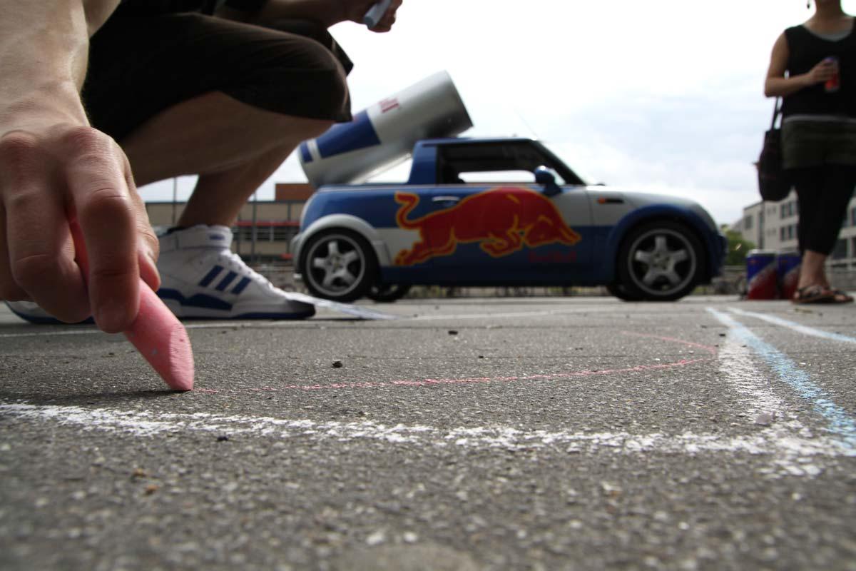 Das Auto von Red Bull für die Guerilla Marketing Aktion von CROMATICS steht vor der Universität Dresden. Mit Kreide wird auf den Boden gemalt.