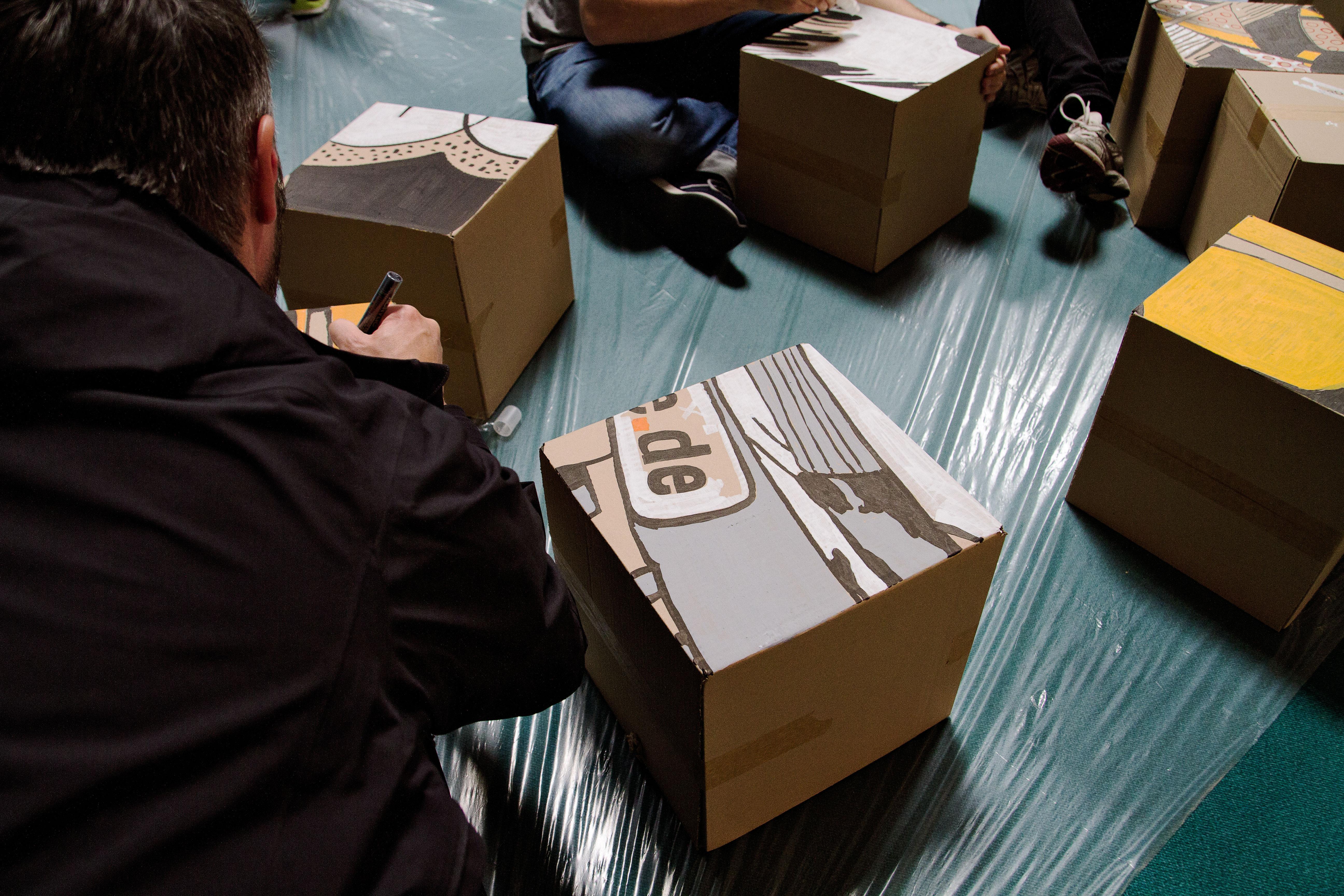 Die Mitarbeiter malen nun die Kartons fertig.
