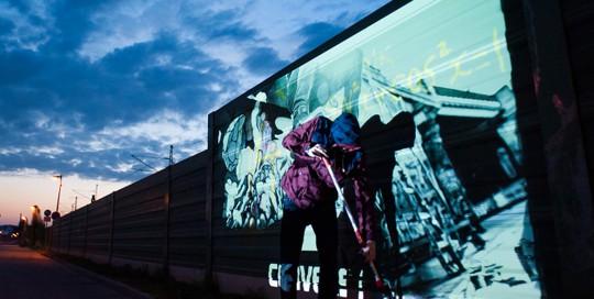 Ein Mitarbeiter von CROMATICS mal mit dem Digital Paintroller auf der Wand. Ein Projektor erfasst den Paintroller und malt mit Licht das Artwork auf die Wand.