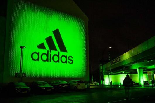 Das adidas Logo erstrahlt einen Berliner Parkplatz. Die Kampagne wird öffentlich zur Schau gestellt.