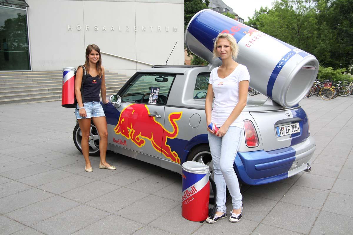2 junge Frauen stehen vor dem Red Bull Auto und machen Werbung für das Air Race 2010